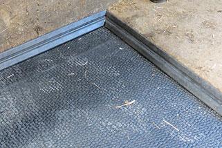 Auf dem Deckbelag werden Abdeckleisten als Abschluss zur Boxenbegrenzung gelegt